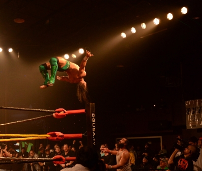 PAC performs a spectacular top rope moonsault onto Brodie Lee