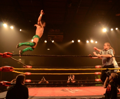 PAC leaps off the top rope towards Brodie Lee